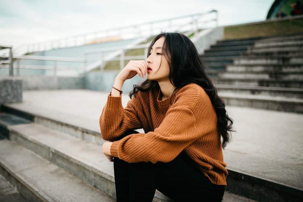 woman wearing brown sweater holding lips