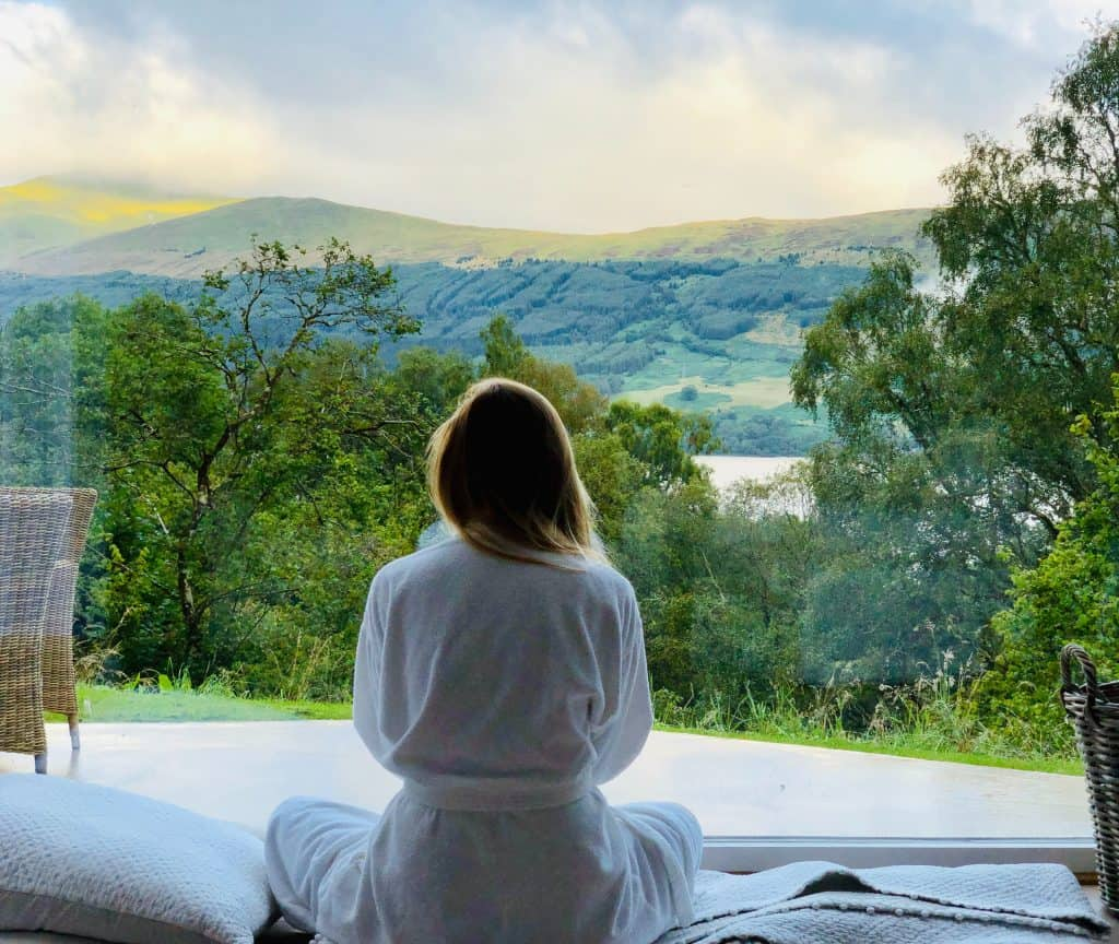 sitting woman in white robe looking at mountains during daytime