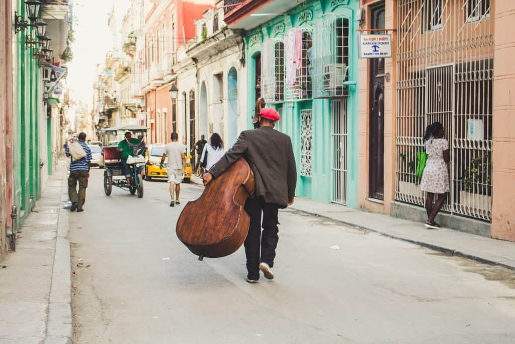 man carrying stringed instrument while walking the pavement during daytime
