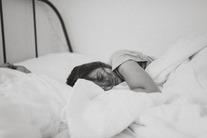 grayscale photo of sleeping woman lying on bed