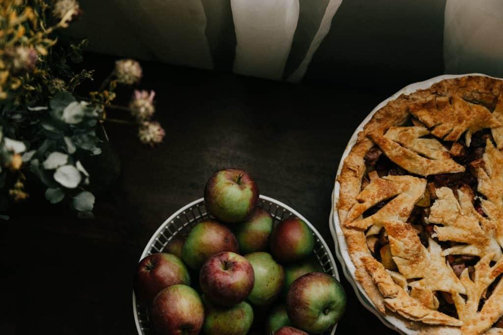 apples on white ceramic bowl